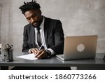 Small photo of a young aspiring African-American investor works at a computer, analyzes the securities market