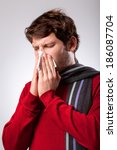 Small photo of Ailing young man suffering from running nose