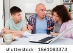 Small photo of Chagrined family with teenage son working with papers at home
