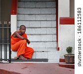 Small photo of BENTOTA, SRI LANKA - 27 APR 2013: Young Buddhist monk sits on a monastery steps in Bentota, Sri Lanka. Sri Lnaka has unambiguous Buddhist majorities in the county.