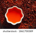 Small photo of Red chilli oil in white porcelain bowl, rad pepper oil