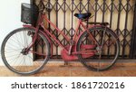 An Old Red Bicycle Parked Next...