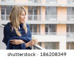 Young Woman Standing On Balcony