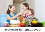 two happy women with child cook ... | Shutterstock . vector #186261920