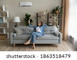 Small photo of Happy young Caucasian woman relax on couch in living room turn on air conditioner with remote controller. Smiling female rest on sofa at home breathe fresh air from ac electronic condition device.