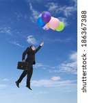Businessman wearing black suit holding suitcase flying in the air being raised by bunch of colorful balloons - stock photo