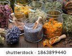 Small photo of Glass jars of dry lavender and calendula flowers. Jars of dry medicinal herbs for making herbal tea, bunch of dry lavender on table. Alternative medicine.