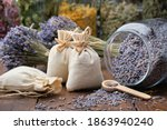 Small photo of Glass jar of dry lavender flowers, sachets, bunches of dry lavender. Jars of different dry medicinal herbs on background. Alternative medicine.