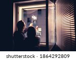 Small photo of Couple holding sparklers out of the window at night. New year's eve celebration, anniversary, party or date at home. Spontaneous candid fun with light firework stick. Happy and playful romantic moment