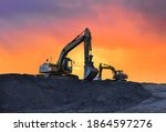 Small photo of Excavator working on earthmoving at open pit mining on amazing sunset background. Backhoe digs sand and gravel in quarry. Heavy construction equipment during excavation at construction site