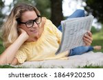 Woman Lying In Grass Reading...