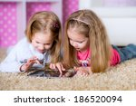 happy sisters using tablet... | Shutterstock . vector #186520094