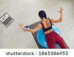Small photo of From above young woman watching sports video lesson on laptop and doing back extension exercise on fit ball with online trainer. Stability training, yoga ball ab workout at home, balance ball therapy