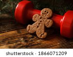 Small photo of Delicious gingerbread man cookie, heavy red dumbbell and Christmas tree branches. Healthy fitness lifestyle holiday season concept composition, cheat day temptation vs sticking to the diet.