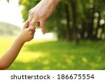 a parent holds the hand of a... | Shutterstock . vector #186675554