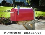 Red rural mailbox on a wooden...