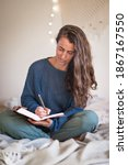 Small photo of Woman in blue sweater writing in leatherbound journal whilst sat on her bed