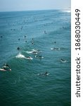 Small photo of HUNTINGTON BEACH, CA, U.S.A. - NOV. 26, 2020: A large group of unmasked surfers paddle out and catch waves on Thanksgiving Day in Huntington Beach