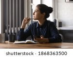 Small photo of Pensive young hindu female study by desk using mobile internet distracted from making notes create new idea. Thoughtful mixed race woman looking aside of phone screen pondering planning future work
