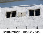 Sundial On The Wall Of A White...