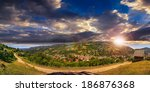 summerlandscape. village on the hillside between the mountain at sunset - stock photo