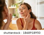 Small photo of Beauty girl looking at mirror while touching her face and checking pimple, wrinkles and bags under the eyes, during morning beauty routine. Happy smiling beautiful young woman applying moisturizer.