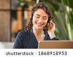 Small photo of Happy young woman working on laptop while talking to customer on phone. Consulting corporate client in conversation with customer using computer. Service desk consultant talking in a call center.