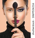 Small photo of Portrait of a girl with cosmetic brush at face. Woman holds a big makeup brush right in the middle of the face. One half face of a beautiful white woman with bright makeup and the other is natural.