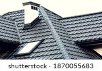 Small photo of Roof of a new house with slants, a skylight, a plastered chimney and ventilation grilles. Roof covering with steel tiles.