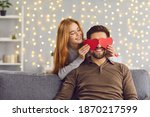 Small photo of Happy smiling couple in love celebrating their relationship anniversary at home. Young people having fun on Saint Valentine's Day. Woman covering boyfriend's eyes with two red heart-shaped cards