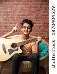 Small photo of Indian asian boy playing acaustic guitar while sitting against white background or brick wala on chair