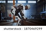 Small photo of Black African American Engineer is Testing a Futuristic Bionic Exoskeleton and Picking Up Metal Objects in a Heavy Steel Industry Factory. Contractor is Heavy Lifting Steel Parts in a Powered Shell.