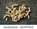 the wooden pellets on old wooden background - stock photo