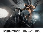 Small photo of Young Man in Face Mask doing Exercise on Spin Bike in dark Fitness Gym. Guy Riding on Spinning Bike. Training during self-isolation COVID. Healthy Lifestyle and Sport Concepts. Functional training.