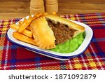 Small photo of Steak and kidney pie and chips meal with mushy peas in a metal enamel dish