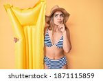 Small photo of Young beautiful blonde woman wearing bikini holding floater serious face thinking about question with hand on chin, thoughtful about confusing idea