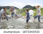 Fathers and children splashing water on each other in the Stream