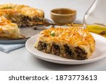Small photo of Rolled Burek - savoury pie fith meat and mushrooms feeling, decorated with sesam seedes. Peace of pie on a white table.