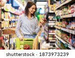 Small photo of Portrait Of Smiling Woman With Shopping Cart In Supermarket Buying Groceries Food Walking Along The Aisle And Shelves In Grocery Store, Holding Glass Jar Of Sauce, Choosing Healthy Products In Mall