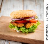 Small photo of Closeup on zinger burger with deep fried chicken on the wooden table