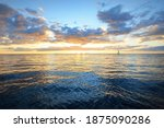 Small photo of Dramatic sunset sky above the sea. Colorful glowing golden clouds, still water surface texture close-up. Sailing after the storm, view from the yacht. Epic seascape. Nature, fickle weather
