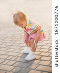 Small photo of fair-haired baby in tennis clothes ties shoelaces at sunset