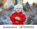 Small photo of Outdoor winter portrait of little cute toddler girl in red coat and white fashion hat barret. Healthy happy baby child walking in the park on cold day with snow and snowfall. Stylish clothes for kids.