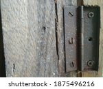 An Old Rusty Hinge On A Wooden...