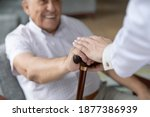 Small photo of Close up of nurse caregiver palms covering hand of smiling senior patient holding cane. Sick old man struggle with trauma consequence make success on rehabilitation therapy with help support of doctor