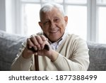 Small photo of Portrait of happy senior grandfather sitting on couch looking at camera demonstrating white healthy teeth in smile. Satisfied elderly man patient having healthy habit of regular visiting dental clinic