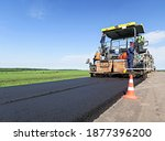 Paver machine on a new asphalt road surface. Road equipment on the construction site for road works. The asphalt surface. Workers and road construction machinery scenes.  Highway on a rural landscape