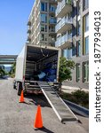 Small photo of Big rig bonnet industrial semi truck with open box trailer stands on the city street near an multi levels apartment building with a lowered gangway and equipment for safety moving