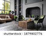 Small photo of Comfort armchairs near wooden table against decorative fireplace, couch, houseplants and home decor in fancy apartment. Elegant living room with stylish and loft interior design