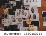 Small photo of Detective board with crime scene photos, stickers, clues and red thread, closeup